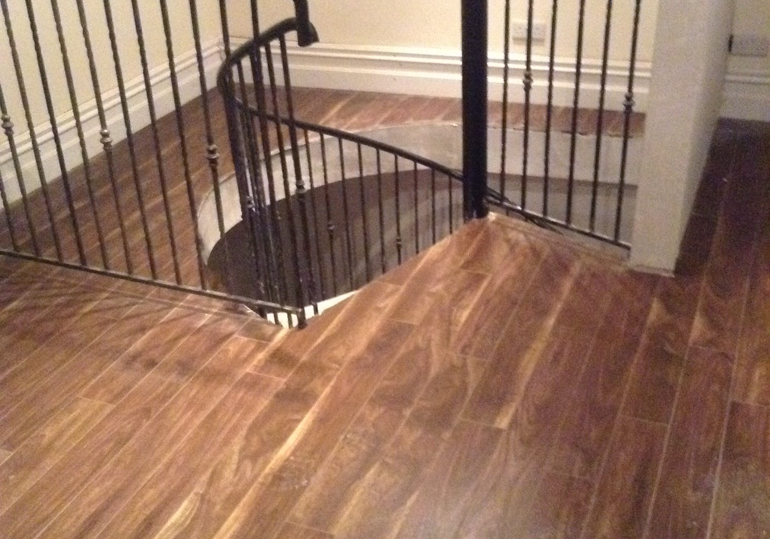 Finished Spiral Staircase with wrought iron handrails and hardwood flooring, in converted Loft